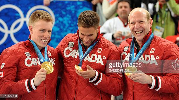 Canada's skip Kevin Martin along with teammates Marc Kennedy and John Morris celebrate on the podium during the medals ceremony after the Vancouver...