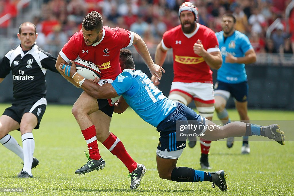TORONTO, ON - JUNE 26 - Canada's Taylor Paris tries to evade a tackle from Italy's David Odiete during the first half of Rugby action as Canadas Mens Rugby Team takes on Italy in a Rugby World Cup (RWC) 2015 re-match on Sunday at BMO field in downtown Toronto June 26, 2016.