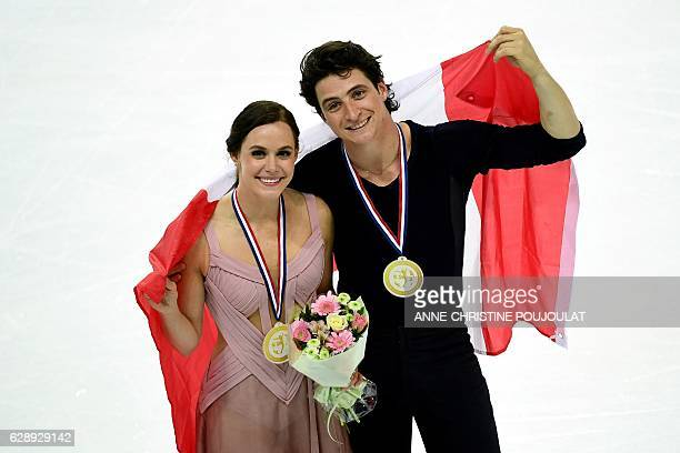 Canada's Tessa Virtue and Scott Moir pose with the Canadian national flag and their gold medals as they celebrate after winning the Senior Ice Dance...