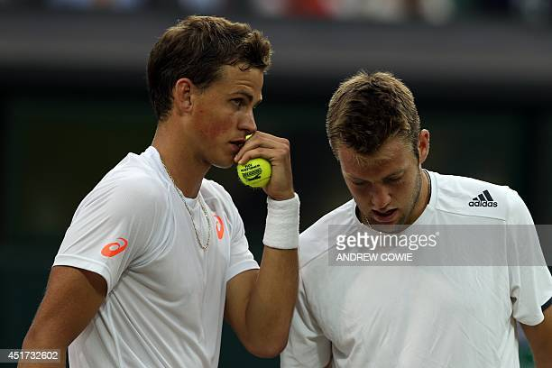 Canada's Vasek Pospisil and US player Jack Sock talk between points against US players Bob and Mike Bryan during their men's doubles final match on...
