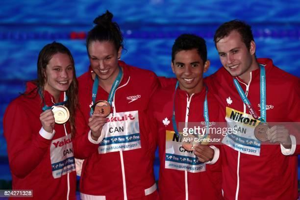 Canada's Yuri Kisil Canada's Javier Acevedo Canada's Chantal van Landeghem and Canada's Penny Oleksiak celebrate on the podium after the mixed 4x100m...