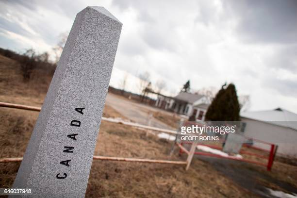 A CanadaUS border marker sits near the abandoned US customs station on Meridian Road in Champlain New York February 27 2017 / AFP / Geoff Robins