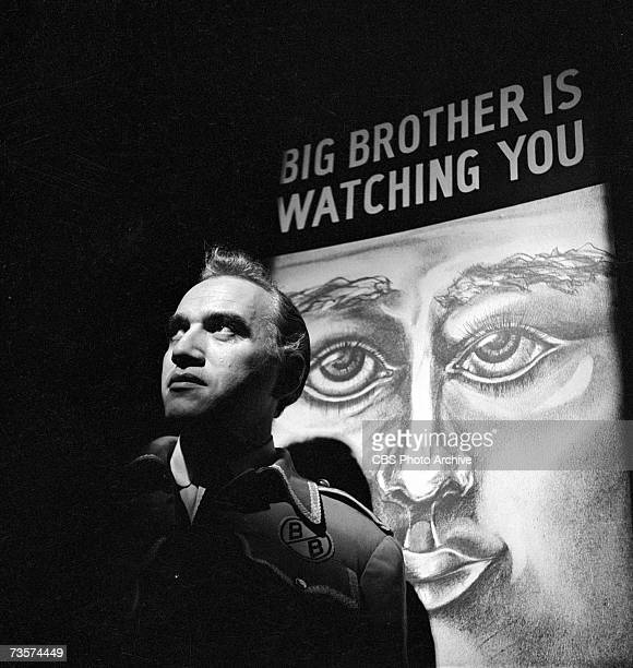 Canadian actor Lorne Greene appears in character as O'Brien in front of a poster which reads 'Big Brother is Watching You' in the episode '1984' of...