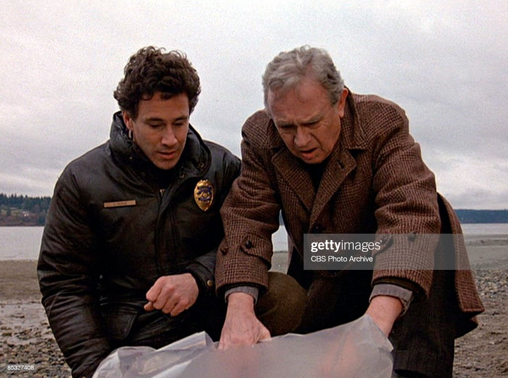 Canadian actor Michael Ontkean (as Sheriff Harry S. Truman) (left) and American actor Warren Frost (as Dr. Will Hayward) talk as they examine a plastic-wrapped body on a rocky beach in a scene from the pilot episode of the television series 'Twin Peaks,' originally broadcast on April 8, 1990.