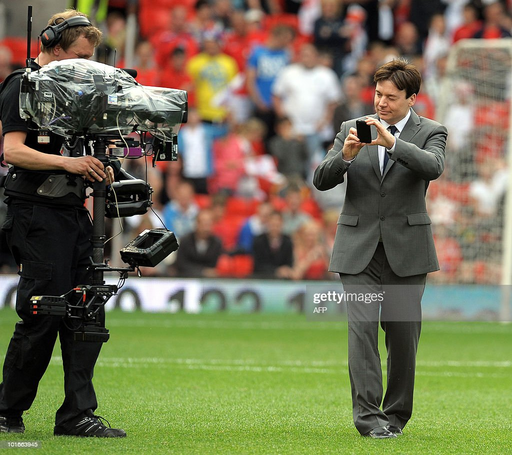 Canadian actor Mike Myers (R) takes photographs a cameraman on the pitch before the Unicef Soccer Aid charity football match at Old Trafford in Manchester, north-west England on June 6, 2010. Soccer Aid is the brainchild of Robbie Williams and all money raised through profits from ticket sales and donations made by viewers of ITV during the match will go to UNICEF�s invaluable work helping children around the world.