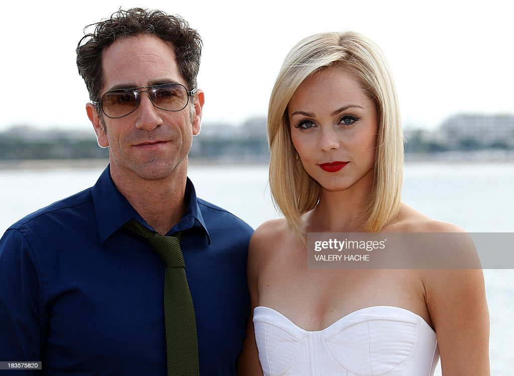 Canadian actress Laura Vandervoort and film director J.B Sugar pose during a photocall for a TV show 'Bitten' as part of the Mipcom international audiovisual trade show at the Palais des Festivals, in Cannes, southeastern France, on October 7, 2013.
