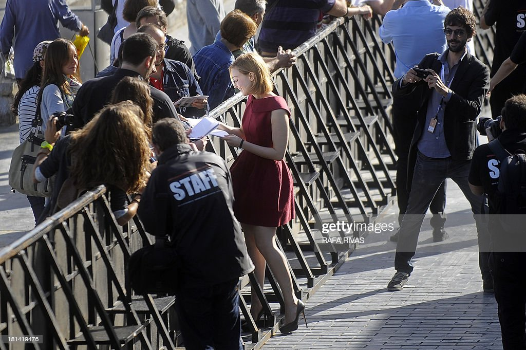 Canadian actress Sarah Gadon (C) signs autographs after the screening of her film 'Enemy' during the 61st San Sebastian International Film Festival in the northern Spanish Basque city of San Sebastian on September 21, 2013.