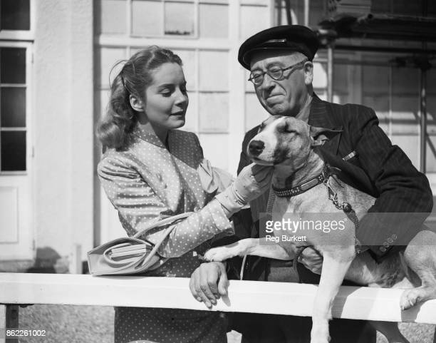 Canadian actress Suzanne Cloutier with costar Gordon Harker and his dog Tom during the filming of 'Derby Day' at Epsom Downs UK 29th August 1951