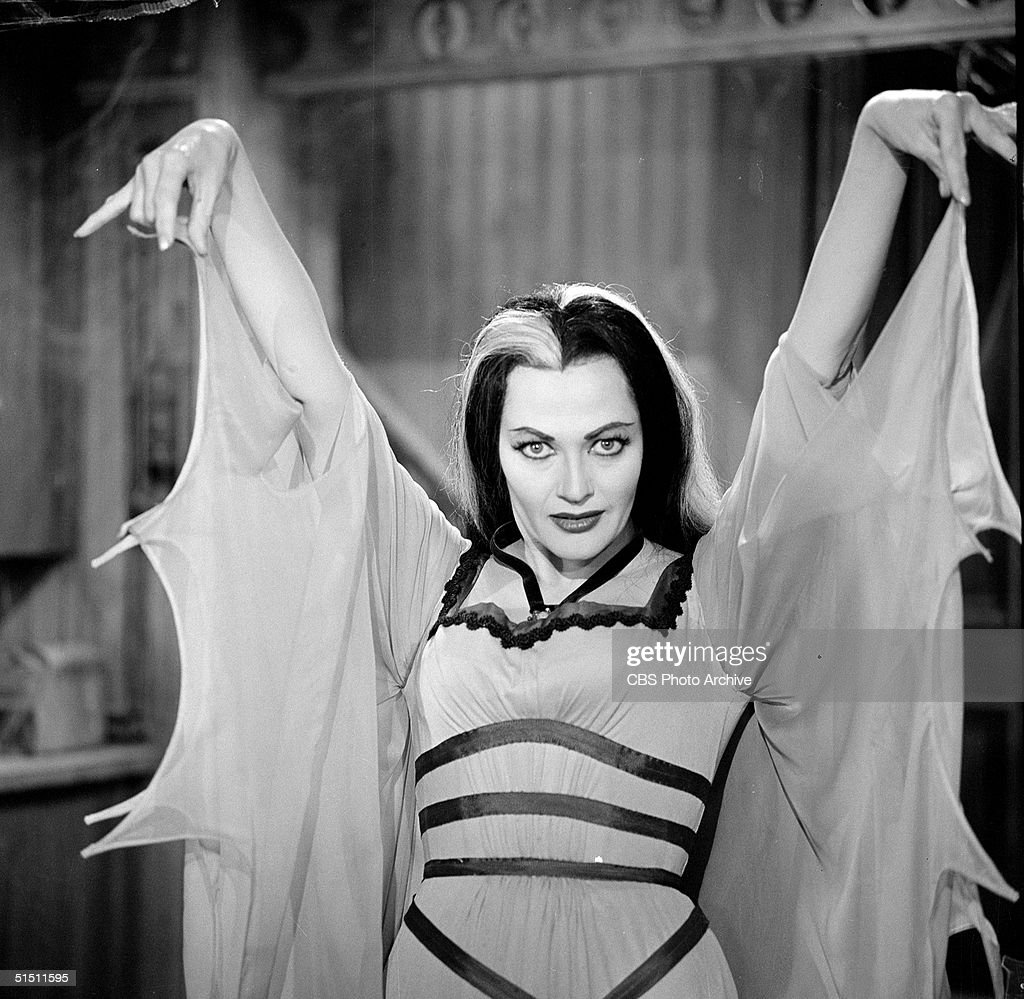 Canadian actress Yvonne de Carlo raises her arms and gestures as she wears a bat-winged dress in her role as 'Lily Munster' in a still from the CBS television situation comedy 'The Munsters' episode 'My Fair Munster,' May 1, 1964.