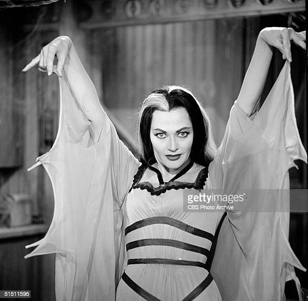 Canadian actress Yvonne de Carlo raises her arms and gestures as she wears a batwinged dress in her role as 'Lily Munster' in a still from the CBS...