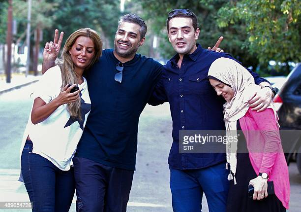 OUT== Canadian AlJazeera journalist Mohamed Fahmy and his colleague Baher Mohamed celebrate with their wives Marwa and Jihan after being dropped off...