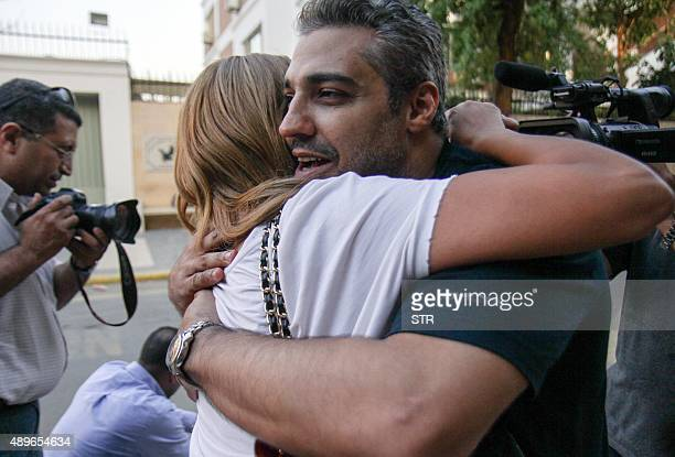 OUT== Canadian AlJazeera journalist Mohamed Fahmy hugs his wife Marwa after being dropped off by authorities in the upmarket Cairo suburb of Maadi...