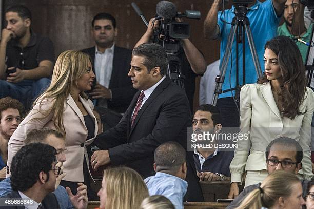 Canadian AlJazeera journalist Mohamed Fahmy hugs his wife Marwa as human rights lawyer representing Fahmy Amal Clooney looks on at the start of his...