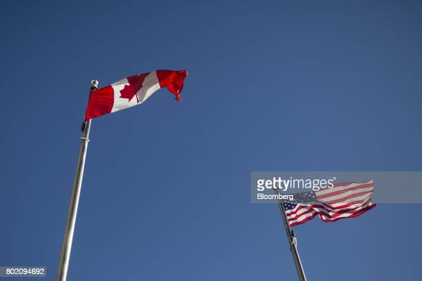 Canadian and American flags fly at the Niagara Falls International Rainbow Bridge in Niagara Falls Ontario Canada on Wednesday June 21 2017 The 150th...
