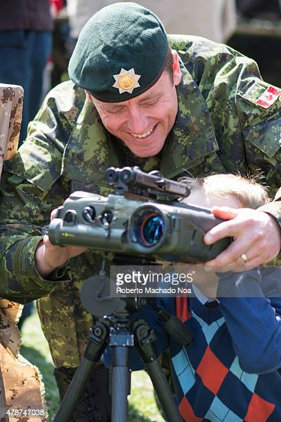 YORK TORONTO ONTARIO CANADA Canadian Army display Smiling soldiers helps boy looks to the military binoculars during the celebration of the 200th...