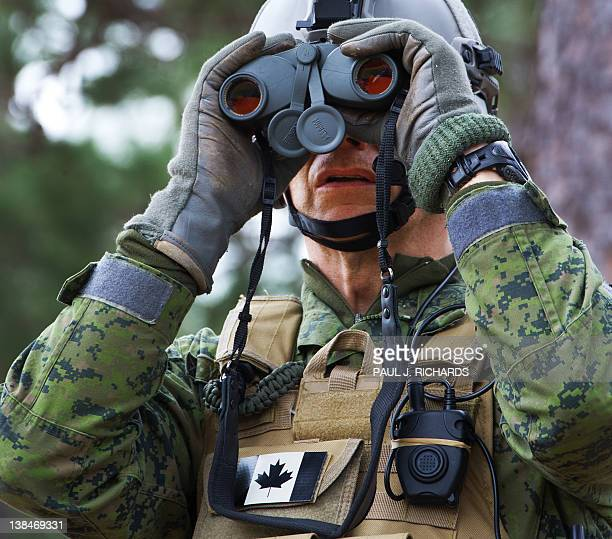 A Canadian Army member watches urban combat by French soldiers after coming ashore February 5 during Operation Bold Alligator 2012 a multinational...