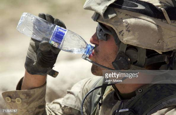 Canadian army soldier drinks water in sweltering heat while conducting a sweep operation for Taliban fighters June 14 2006 in Panjwai 30 kilometers...