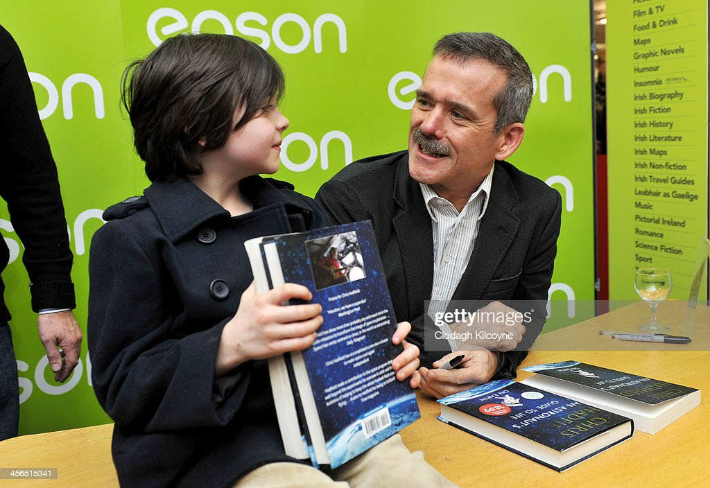 Canadian astronaut Chris Hadfield signs a copy of his book 'An Astronaut's Guide to Life on Earth' for young fan Luke Lally, aged 7, who had been queueing since 5 am to meet him, in Eason book shop on O'Connell Street on December 14, 2013 in Dublin, Ireland.