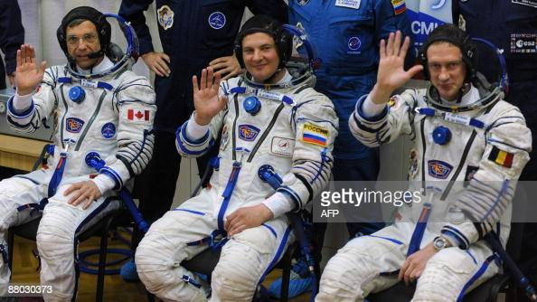 Canadian astronaut Robert Thirsk European Space Agency astronaut Frank De Winne of Belgium and Russian cosmonaut Roman Romanenko wave after putting...