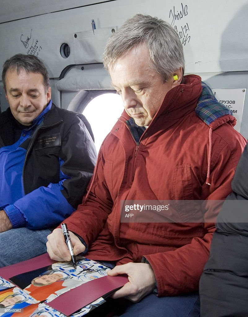 Canadian astronaut Robert Thirsk (R) signs an autograph as he travels by helicopter from Arkalyk to Kostanay in northern Kazakhstan on December 2, 2009. The Russian Soyuz space capsule, carrying Belgian Frank de Winne, Thirsk and Russian Roman Romanenko, landed as planned at 10:17 a.m. Moscow time (0717 GMT) on November 1 about 85 km (50 miles) north of the town of Arkalyk in Kazakhstan.