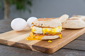 Canadian Bacon, egg and cheese breakfast sandwich with english muffin on cutting board with running yoke