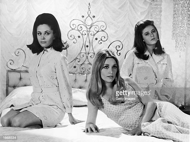 Canadian born actor Barbara Parkins and American actors Sharon Tate and Patty Duke sit on a bed in a still from the film 'Valley of the Dolls'...