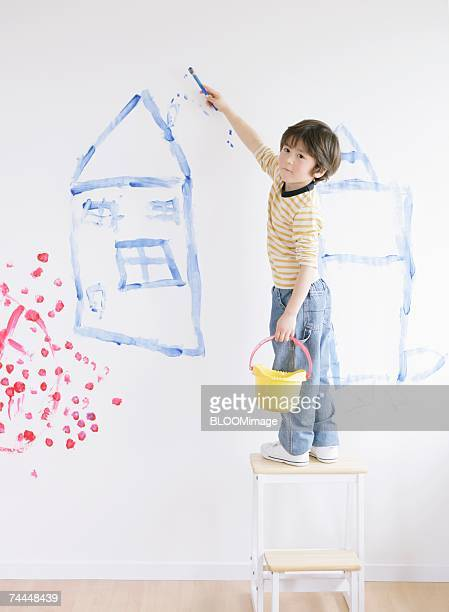 Canadian boy drawing picture on wall in room
