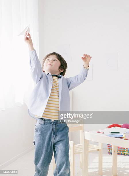 Canadian boy playing with plane of paper