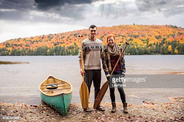 Canadian couple with a canoe in the park during fall