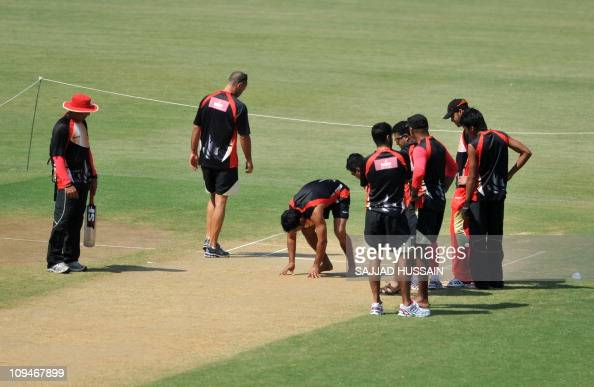 Canadian cricketers inspect the pitch during a practice session at The Vidarbha Cricket Association Stadium Stadium in Nagpur on February 27 2011...