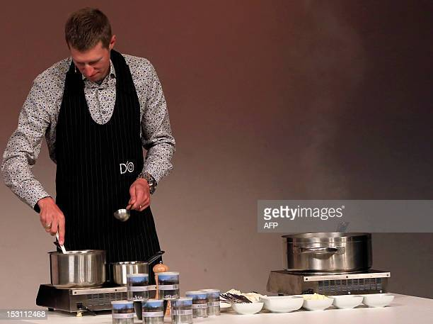 Canadian cyclist Ryder Hesjedal takes part in a kitchen test during the presentation of the 96th Giro d'Italia 2013 route on September 30 in Milan...