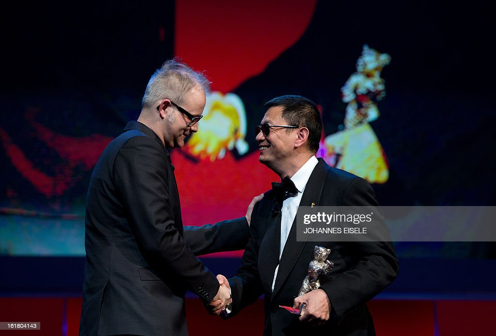 Canadian director Denis Cote (L) receives his Alfred Bauer Silver Bear award for the movie 'Vic+Flo ont vu un ours' (Vic+Flo Saw a Bear) from Hong Kong Chinese director Wong Kar-Wai, jury president during the awards ceremony of the 63rd Berlinale Film Festival, in Berlin on February 16, 2013. AFP PHOTO / JOHANNES EISELE