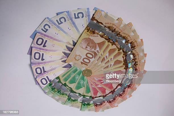Canadian dollar bills are arranged with a coin for a photograph in Toronto Ontario Canada on Tuesday Feb 26 2013 Canada's dollar traded at almost the...