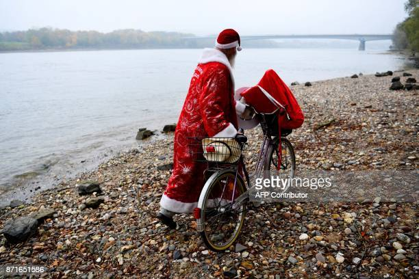 Canadian environmentalist Philip McMaster dressed up as Santa Claus pushes his bicycle on the shore of the Rhine river on November 8 2017 in Bonn...
