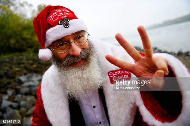 Canadian environmentalist Philip McMaster dressed up as Santa Claus gestures as he answers AFP journalists' questions on the shore of the Rhine river...
