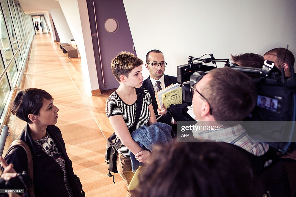 Canadian feminist artist Rosea Lake Rosea Lake (C) speaks to reporters on October 8, 2013 in Antwerp after a preliminary injunction against a Flemish far-right party Vlaams Belang campaign. Lake filed a complaint following a Vlaams Belang campaign, claiming plagiarism of her 'Judgments' creation by Flemish group 'Women against Islamisation,' showing the bare legs of an ex-Miss Belgium wearing signature red-soled Louboutins as she lifts up a black dress. Words etched along the naked leg mark potential skirt lengths -- ranging from 'Sharia compatible' at the ankle to 'stoning' high up a thigh.