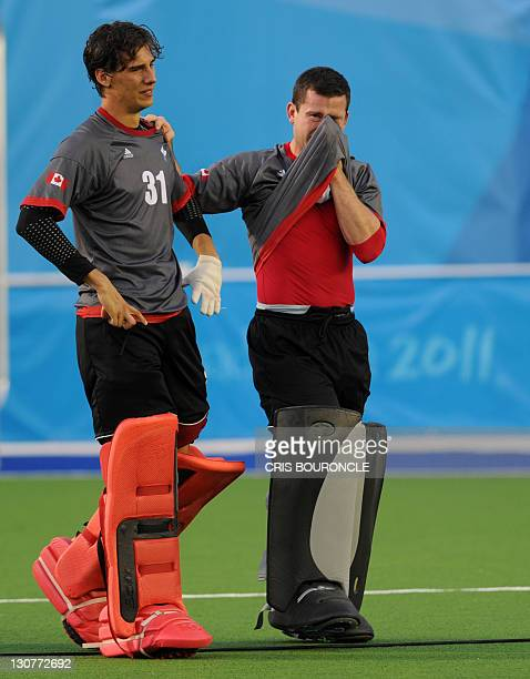 Canadian field hockey goalkeepers Antoni Kindler and David Carter walk out of the pitch in dejection after losing the final game for the gold against...