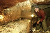 Canadian filmmaker Simcha Jacobovici examines a burial niche inside the Talpiot tomb in Jerusalem Israel in this undated handout photo from Vision TV...