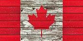 Canadian flag painted on a weathered rustic wood background