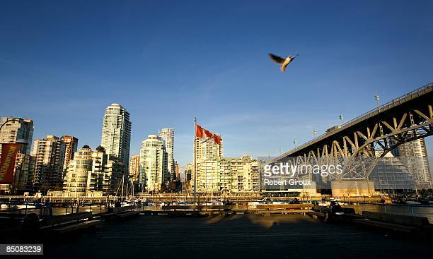 Canadian flag waves in the wind as the sun sets on the city skyline on February 18 2009 in Vancouver British Columbia Canada Vancouver is the host...