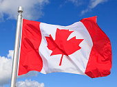 Canadian flag waving on the wind with blue sky and white clouds on the background, Quebec, Canada