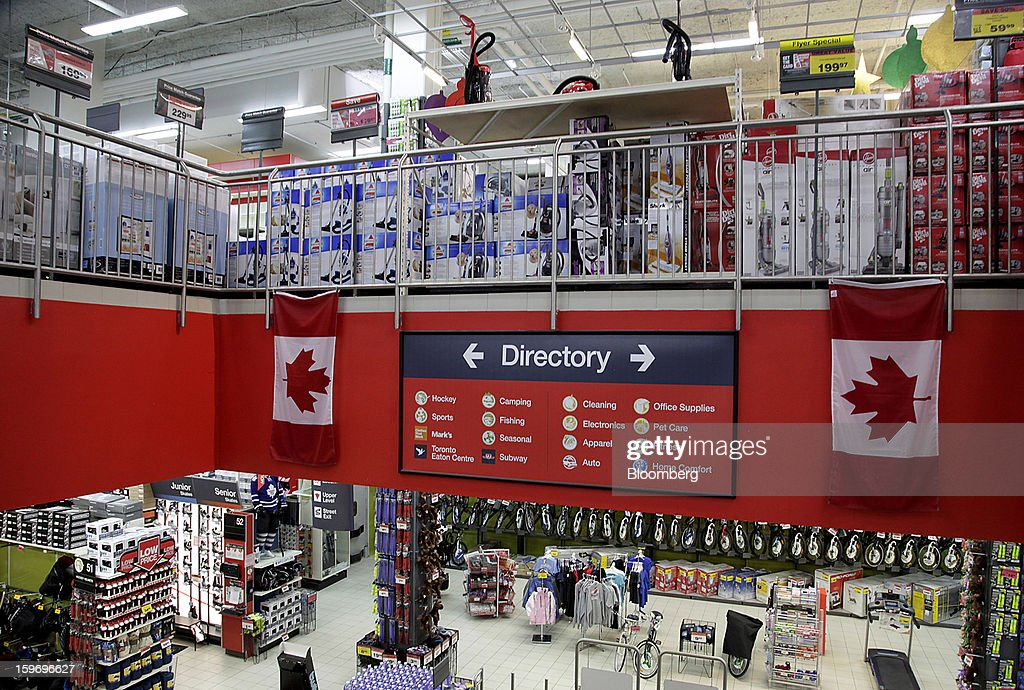 Canadian flags hang next to the directory inside of a Canadian Tire Corp. store in Toronto, Ontario, Canada, on Friday, Jan. 18, 2013. STCA - Statistics Canada is scheduled to release retail sales data on Jan. 21. Photographer: Reynard Li/Bloomberg via Getty Images