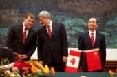 Canadian Foreign Minister John Baird whispers to Canadian Prime Minister Stephen Harper while standing next to Chinese Premier Wen Jiabao during a...