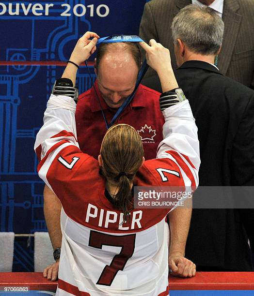 Canadian forward Cherie Piper gives her medal to a coach after team Canada received their gold medals during the medals ceremony in the Woman's Ice...