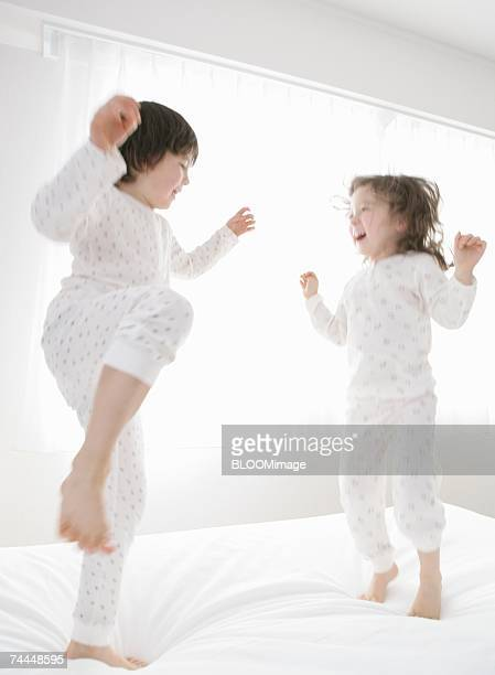 Canadian girl and boy playing on bed