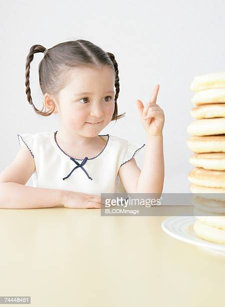 Canadian girl counting piling pancakes on table