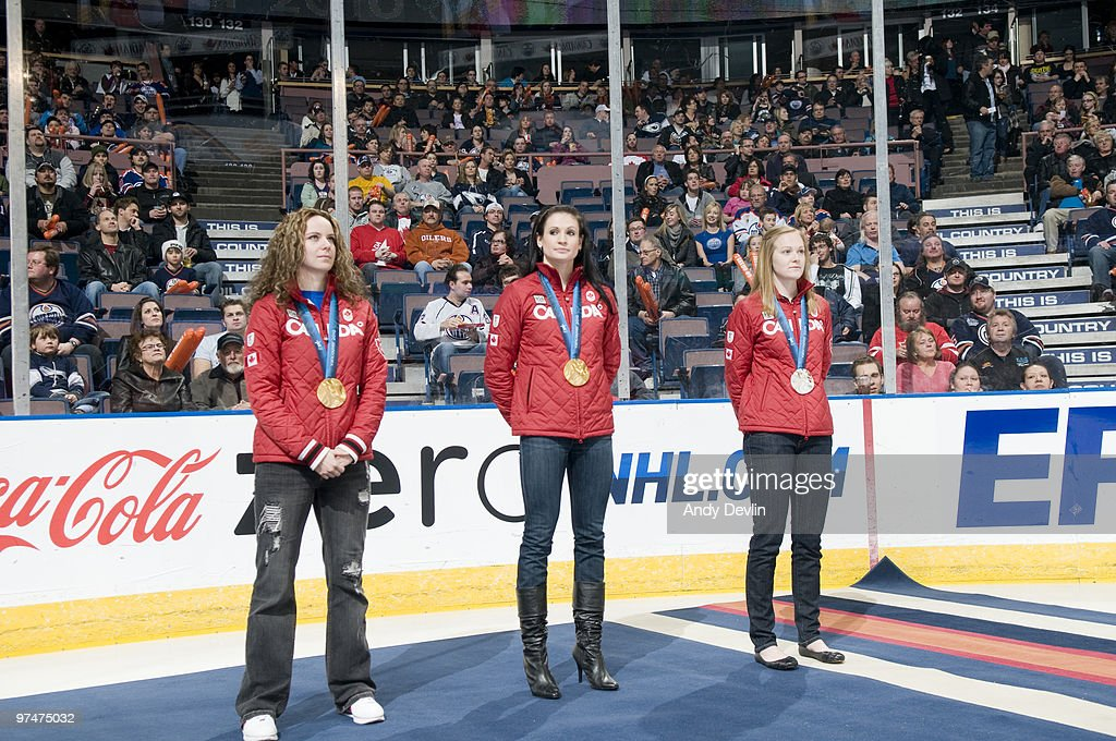 Canadian gold medallists Shannon Szabados Meaghan Mikkelson and Jessica Gregg are saluted by the crowd before a game between the Edmonton Oilers and...