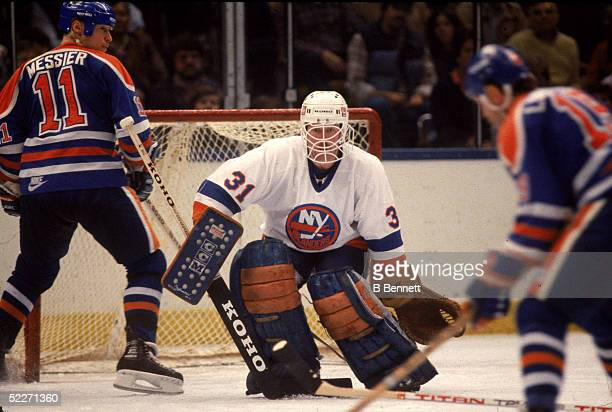 Canadian hockey player Billy Smith in the uniform of the New York Islanders prepares for a shot by the Edmonton Oilers' Willie Lindstrom during a...