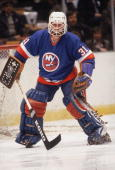 Canadian hockey player Billy Smith in the uniform of the New York Islanders guards the net during a road game 1980s