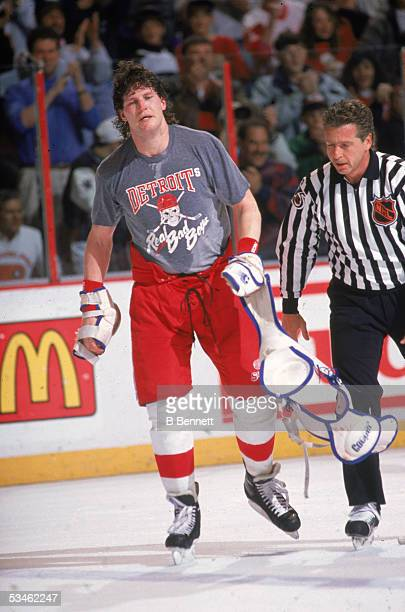 Canadian hockey player Bob Probert of the Detroit Red Wings pads in his hands is escourted off the ice by an official after a fight at the Spectrum...